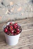 Ciliege rosse in secchio bianco sulla tavola di legno Cibo sano del raccolto della primavera Frutta Immagini Stock