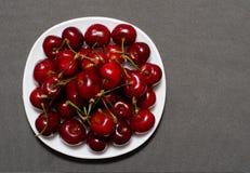 Ciliege rosse su un piatto, fondo grigio strutturato, spazio per testo Fotografia Stock