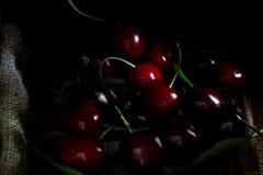 Ciliegi rossi e dolci con le foglie su fondo di legno immagini stock libere da diritti