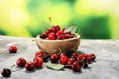 Ciliegia Ciliege fresche rosse in ciotola e un mazzo di ciliege su Th Immagine Stock