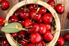 Ciliegia Ciliege fresche rosse in ciotola e un mazzo di ciliege su Th Fotografia Stock Libera da Diritti