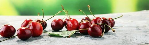 Ciliegia Ciliege fresche rosse in ciotola e un mazzo di ciliege su Th Immagini Stock