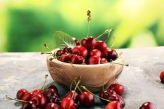 Ciliegia Ciliege fresche rosse in ciotola e un mazzo di ciliege su Th Fotografie Stock Libere da Diritti