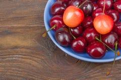 Ciliegia fresca di varia estate in una ciotola sulla tavola di legno rustica Antiossidanti, dieta della disintossicazione, frutti Immagine Stock
