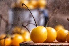 Ciliegia gialla in uno stile rustico su un fondo di legno Bacche delle ciliege fresche mature in una tazza fotografie stock libere da diritti