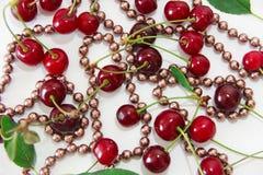 Ciliegia rossa con le foglie verdi e le perle rosa fotografia stock libera da diritti