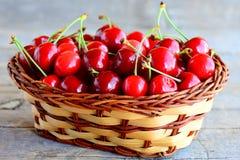 Ciliegia rossa in un canestro di vimini marrone e su una tavola di legno d'annata Concetto di stagione della ciliegia di estate c Fotografia Stock