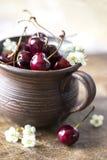 Ciliegia in una tazza dell'argilla con i fiori Fotografie Stock Libere da Diritti