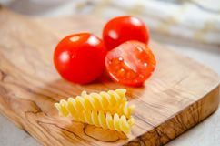 Cherry tomatoes on wooden stong. Ciligino tomatoes on olive wood cutting board with napkin and cutlery on white table Royalty Free Stock Images