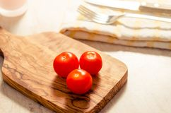 Cherry tomatoes on wooden stong. Ciligino tomatoes on olive wood cutting board with napkin and cutlery on white table Stock Photos