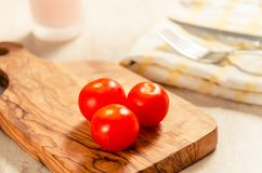 Cherry tomatoes on wooden stong. Ciligino tomatoes on olive wood cutting board with napkin and cutlery on white table Stock Photo