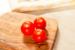 Cherry tomatoes on wooden stong. Ciligino tomatoes on olive wood cutting board with napkin and cutlery on white table Stock Image