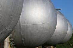 Cilindri d'acciaio giganteschi nello stoccaggio dei materiali infiammabili o Immagine Stock