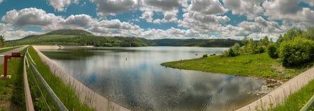 Cilindrisch 180 graadpanorama van een dam in Harz met een dammuur, een oeverstrook met gras en een de zomer blauw-witte hemel, royalty-vrije stock fotografie