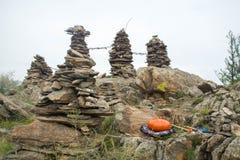 Cilindro de aço da língua na frente das colunas da rocha dedicadas a uma deidade tutelar local fotografia de stock