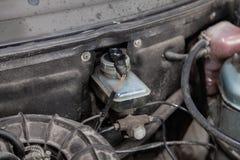 Cilindro de freio do tanque manchado com óleo com um sensor nivelado e os eletricistas dos fios no compartimento de motor do carr foto de stock