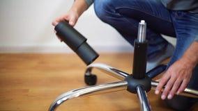 Cilindro de gas del hombre y base de junta de la silla de la oficina junto en casa almacen de metraje de vídeo