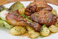 Cilindro grelhado da galinha em batatas fritadas fotografia de stock