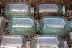 Cilindros de vidro velhos de três litros empilhados nas fileiras Imagens de Stock Royalty Free