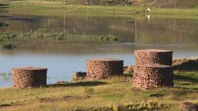 Cilindros do tijolo ao lado da água vídeos de arquivo
