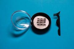 Cils faux magnétiques artificiels réglés sur le fond bleu photographie stock libre de droits