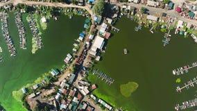 Cima aerea giù delle sponde del fiume nel villaggio del pescatore con le alghe verdi in acqua archivi video