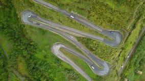 Cima aerea giù la guida di veicoli sulla strada tortuosa, fuco sopra la strada della montagna archivi video