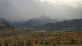 Cima de la montaña de niebla con las nubes de lluvia que pasan cerca almacen de metraje de vídeo