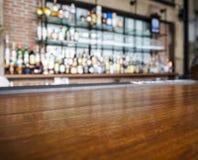 Cima del contatore di legno della tavola con il fondo vago della barra Immagini Stock Libere da Diritti