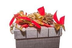 Cima del contenitore di regalo decorata con gli archi e le pigne di rosso Fotografie Stock Libere da Diritti