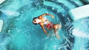 Cima del punto di vista di bella giovane donna di abbronzatura in bikini ed occhiali da sole che gode dello stagno di lusso del g stock footage