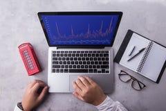 Cima dell'uomo d'affari che per mezzo del computer portatile con il mercato di riserva del grafico sullo schermo fotografia stock