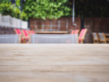 Cima della tavola di legno con il fondo vago del caffè del ristorante Fotografia Stock Libera da Diritti