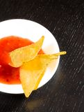 Cima della vista dei nacho croccanti del cereale con salsa al pomodoro calda piccante come uno spuntino o aperitivo in un disco b Immagini Stock