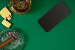 Cima della vista del sigaro in un portacenere vicino al vetro del whiskey sulla tavola verde della mazza Immagine Stock