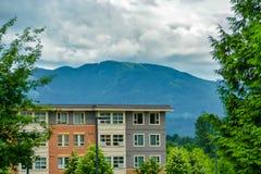 Cima di edificio residenziale sul fondo del cielo nuvoloso e della montagna fotografie stock libere da diritti