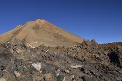 Cima di Teide con la pietra della lava in priorità alta e contro un cielo blu Immagini Stock