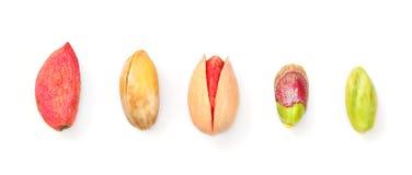 Cima giù la vista, pistacchi nelle fasi diverse da crudo, da parte a parte arrostite e salate a verde sbucciato, isolato su fondo fotografia stock