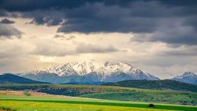 Cima innevata della montagna contro un contesto delle nuvole temporalesche e dei giacimenti di grano di estate 4K Timelaps archivi video