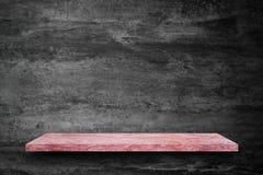 Cima vuota della tavola di pietra di marmo rosa sul fondo del muro di cemento immagine stock