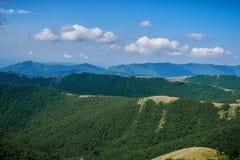 Cime delle montagne sotto il cielo blu Fotografia Stock