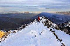 Cimeira da montanha e caminhante distante que olham o por do sol no inverno fotografia de stock royalty free