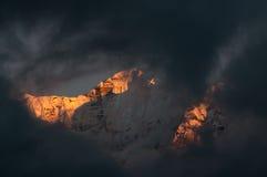 Cimeira nevado brilhante através das nuvens Fotos de Stock Royalty Free