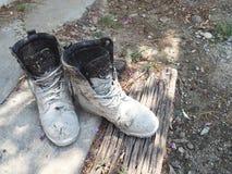 Ciment blanc de tache de bottes Placé sur de vieux déchets de bois et plancher de ciment Photo libre de droits