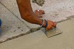 Ciment de truelles de travailleur de Concerete Photo libre de droits