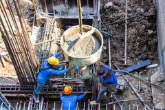 Ciment se renversant de travailleur se renversant dans des bases le coffrage au secteur de bâtiment dans le chantier de construct photos libres de droits