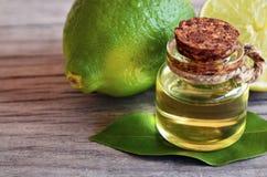 Cimente o óleo essencial em uma garrafa de vidro com frutos frescos do cal Conceito dos termas, da aromaterapia e do bodycare foto de stock royalty free