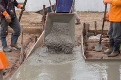 Cimento de derramamento do trabalhador do carro a pavimentar imagem de stock