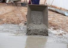 Cimento de derramamento do trabalhador do carro a pavimentar foto de stock