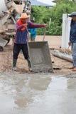 Cimento de derramamento do trabalhador do carro a pavimentar no canteiro de obras imagens de stock royalty free